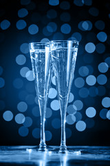 Fototapete - Two glasses of champagne on classic blue bokeh background. Holiday concept. Festive bokeh background. Vertical, toned