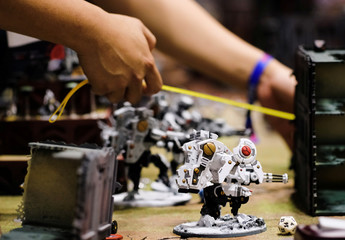 An attendee takes measures while constructing tabletop gaming figurines and props during the Singapore Comic Con, in Singapore