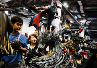 Attendees look at figurines on display during the Singapore Comic Con, in Singapore