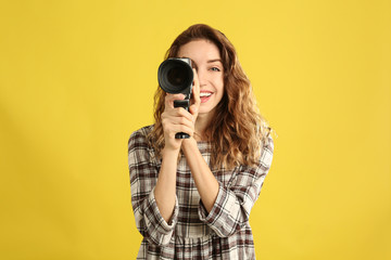 Beautiful young woman with vintage video camera on yellow background