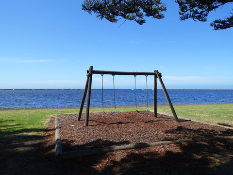 Empty children swing set on a public wood mulch playground by blue sea on a sunny day. Port MacDonnell, SA Australia.