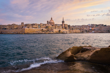 Malta. Valletta seafront at sunset with Basilica of Our Lady of Mount Carmel, viewed from Sliema.