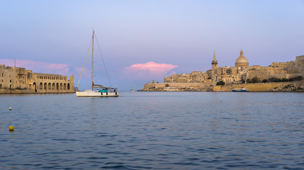 Malta. Valletta skyline at sunset with Basilica and Lazzaretto of Manoel Island, viewed from Ta Xbiex