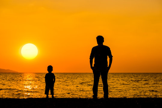 Silhouette father and son stand on the beach at sunset time  with beautiful sun sky background.