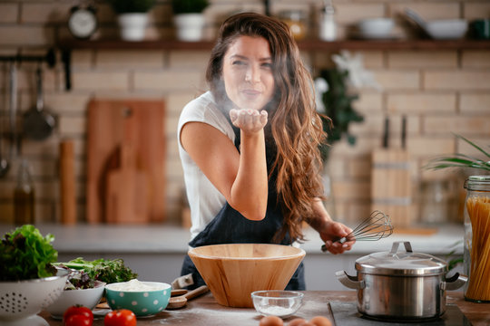 Young woman in kitchen. Beautiful woman playing with flour.
