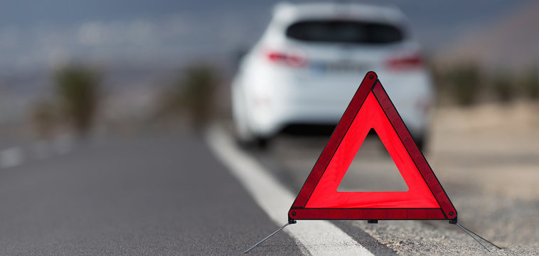 Broken down car with warning triangle behind it waiting for assistance to arrive, red triangle of a car on the road
