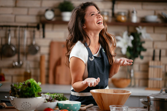 Young woman in kitchen. Beautiful woman having fun while making  dough.