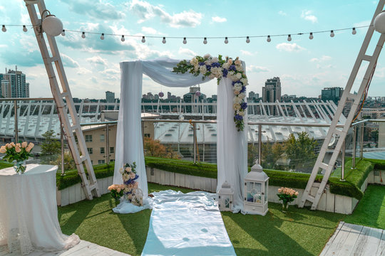 White wedding arch with flowers on building roof in megapolis center under the open sky on sunny day in summer, Kiev, Ukraine. Background is downtown and Olimpijskij stadium. Beautiful view