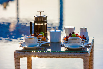 Serving table with fruits and coffee near the outdoor pool.