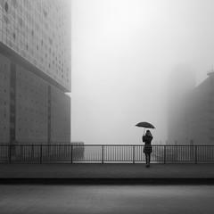 Girl with umbrella in Hamburg Hafencity with fog