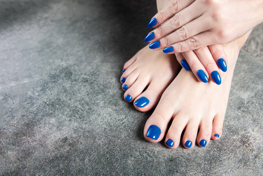 Young lady is showing her blue manicure and pedicure nails, dark grey background, copy space