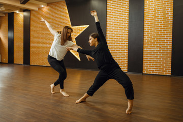 Two contemporary dance performers poses in studio