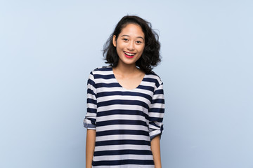 Asian young woman over isolated blue background with surprise facial expression