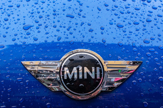 mini cooper logo on the blue metallic car hood.  wet vehicle after the rain