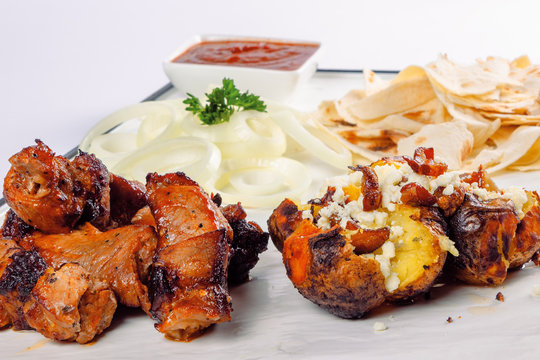 grilled pork and baked potato with cheese. onion circles and pita bread, red sauce on a white board. great snack dish for beer. close up view