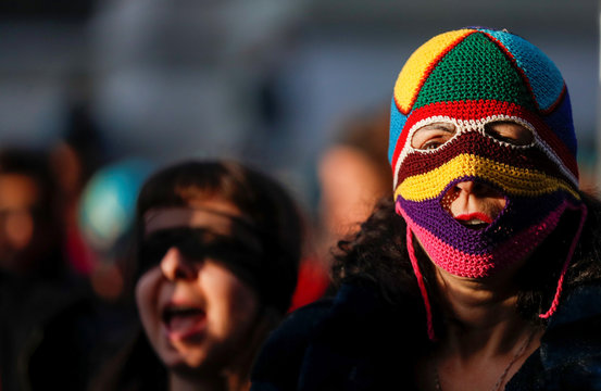 "Women rights activists wear maksk and blindfolds while they sing a song ""the rapist is you"", that became famous in Chile, in front of the Palace of Justice in Rome"