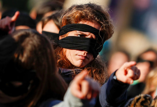 A women rights activist wears a blindfold during a protest in front of the Palace of Justice in Rome