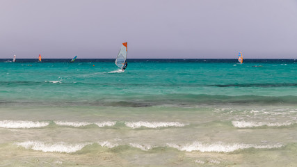 Wind surfers in the sea with turquoise water. Holidays, active lifestyle.