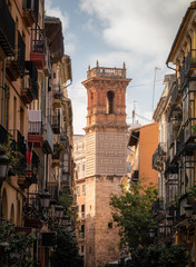 Typical street of Valencia with a historic tower in the background, Spain