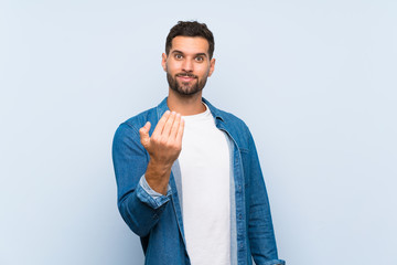 Handsome man over isolated blue background inviting to come with hand. Happy that you came