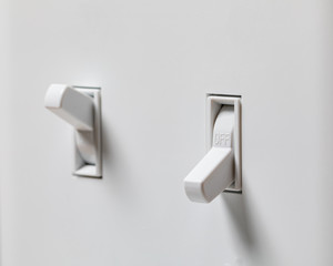 Closeup of white duplex light switch turned off and another turned on in background. Concept of energy saving, conservation