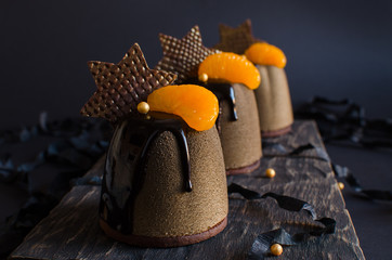 Contemporary chocolate and orange mousse mini cakes decorated with chocolate stars on dark background