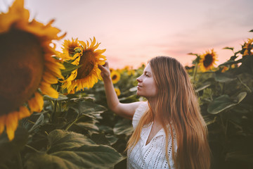 Poster Zonnebloem Woman in sunflowers field harmony with nature travel healthy lifestyle outdoor agriculture organic harvest ecology concept