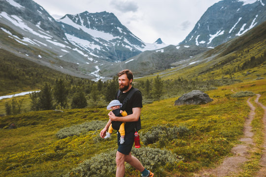 Father hiking with baby carrier travel family lifestyle adventure vacations with child in mountains outdoor in Norway