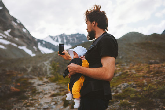 Father with baby carrier hiking in mountains travel family adventure vacations with kids healthy lifestyle outdoor in Norway blogger influencer modern online technology