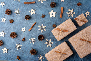 Winter flat lay with cinnamon, anise, cones, wooden snowflakes and gifts in craft paper on a blue textural background. Concept for Christmas and New Year.