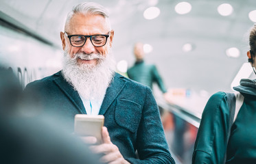Hipster bearded man using mobile smart phone at shopping mall elevators - Trendy old person sharing content with smartphone - Happy lifestyle and technology concept without age limits - Azure filter