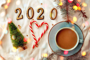 Blue cup with cappuccino in the New Year decoration. New Year 2020, bokeh.