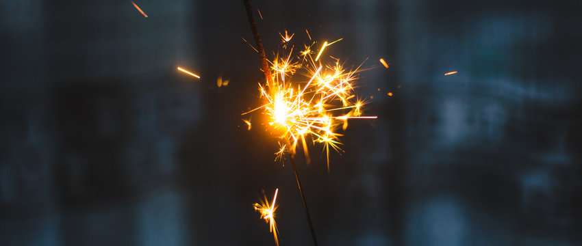 Sparklers for Christmas and New Year close-up in the form of a banner and on a blue background