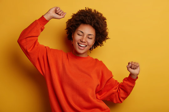 Photo of joyful brunette woman has fun and dances with hands raised, dressed in casual jumper, cheers over yellow background, gets promotion or approval, celebrates win. People and happiness