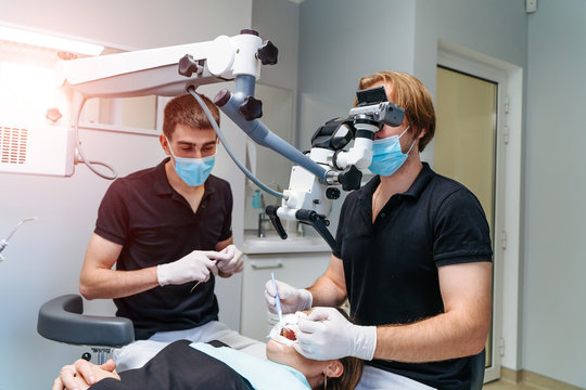 Male dentist with dental tools - microscope, mirror and probe treating patient teeth at dental clinic office. Medicine, dentistry and health care concept. Dental equipment
