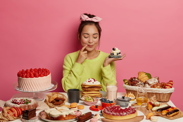Pleased brunette woman holds small creamy muffin, bakes many desserts for New Year holiday or festive time, demonstrates her culinary abilities, has special occasion, degustates homemade cupcake Fototapete