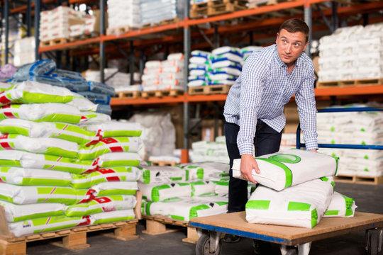 Male buyer storing fertilizer bags on trolley in hardware store