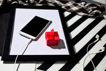 White smartphone and headphones with a red gift box