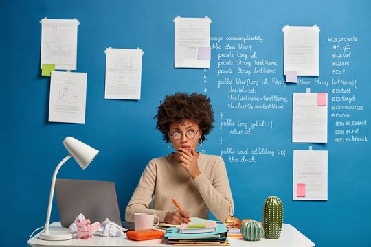 Thoughtful attractive woman in spectacles writes in diary to do list of goals, makes notes in personal organizer, poses at cozy coworking space, creats article on scientific topic, thinks at plans