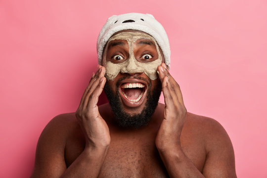 Joyous dark skinned man has funny expression, wears nourishing clay mask, keeps mouth opened, being well groomed, stands with naked torso, has healthy skin. Spa, dermatology, wellness concept