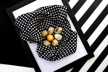 One golden quail egg among a group of eggs in a black frame on an abstract black and white background.