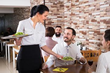 Smiling waitress serving meal for restaurant guests