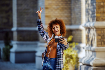 Charming cheerful young mixed race woman with curly hair, in plaid shirt and with headphones around neck standing in front of old building and taking selfie.