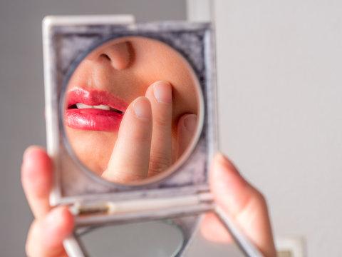 Femme asiatique se maquillant dans un miroir en gros plan