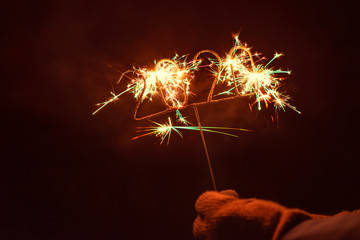 Human hand with glove holding an igniting 2020 Shaped Sparkler, outdoors at night