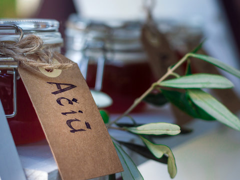 """Small glass jars filled with honey, decorated with eucalyptus and a writing attached to them saying """"Thank you"""""""