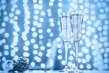 Fototapete - Two glasses of champagne with Christmas toys. Festive lights blue bokeh Christmas background. New Year holidays celebration. Horizontal, toned
