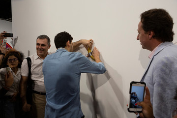 An Art Basel worker attaches a banana with duct-tape in the wall where the artwork 'Comedian' by the artist Maurizio Cattelan was exhibited in Miami Beach