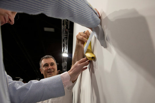 Gallery owner Emmanuel Perrotin attaches a banana with duct-tape on the wall where the artwork 'Comedian' by the artist Maurizio Cattelan was exhibited in Miami Beach