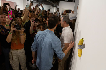 Art Basel visitors use their phones in front of a banana attached with duct-tape that replaces the artwork 'Comedian' by the artist Maurizio Cattelan, which was eaten by David Datuna, in Miami Beach